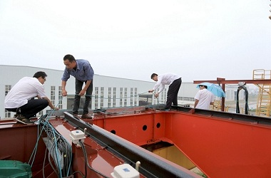 Technical staff inspecting electrical assembly of the cabin, debugging anti-sway program of the crane